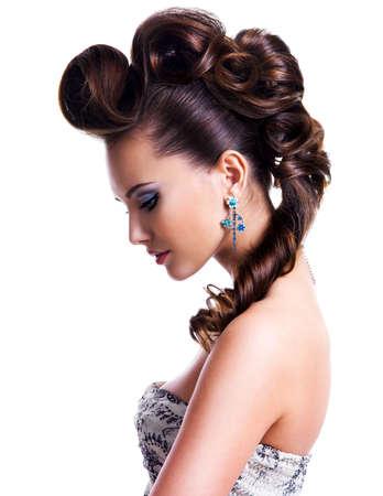 創造的な髪型と明るい着色された目のメイクの美しい若い女性の横顔の肖像画。ファッション モデル着用ブルー ピアス、イヤリング、ネックレスの白で隔離