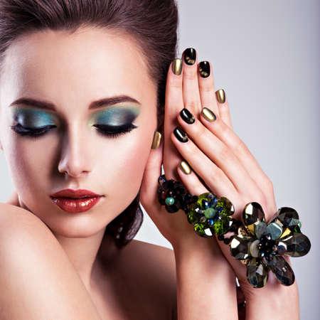 maquillaje de ojos: Mujer hermosa cara con maquillaje verde y joyas de vidrio, clavos creativos Foto de archivo