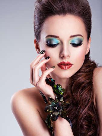Bello fronte della donna con la moda verde make-up e gioielli a portata di mano