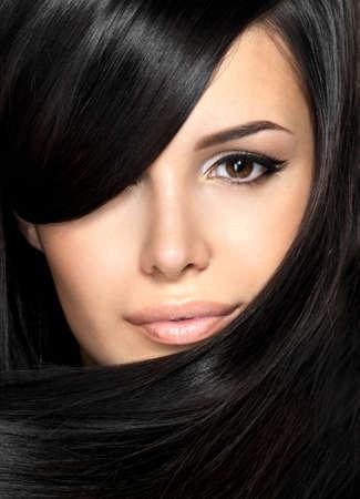 black hair: Mujer hermosa con el pelo liso. Retrato del primer de un modelo de moda posando en el estudio.