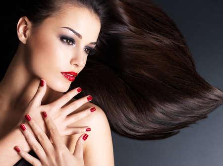 Mooie vrouw met lange bruine rechte haren en rode nagels liggen op de donkere achtergrond