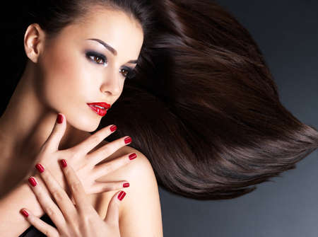 Beautiful woman with long brown straight hairs and red nails lying on the dark background