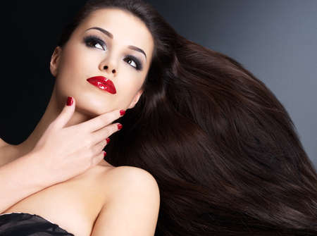 women hair: Beautiful woman with long brown straight hairs and red nails lying on the dark background