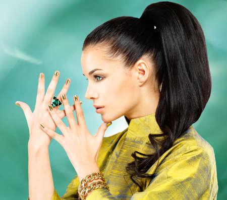 schöne frauen: Fashion Frau mit goldenen Nägeln und schönen Smaragdring