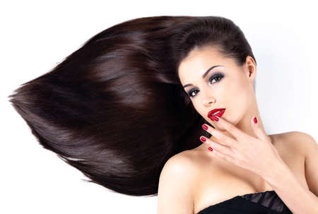 Beautiful woman with long brown straight hairs and elegance red nails