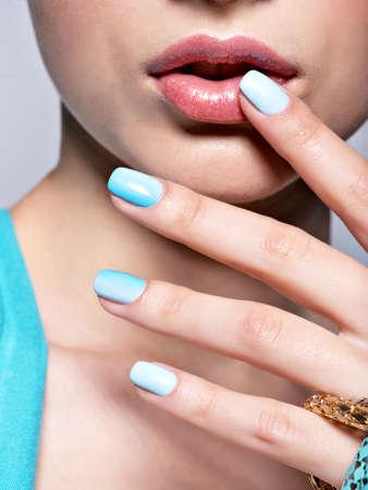 manicura: manos de la mujer manicura u�as azul de la joyer�a de moda. Manos femeninas con u�as azules Foto de archivo