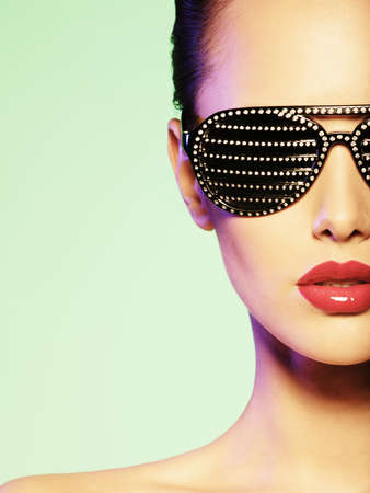 beautiful model: Fashion portrait of  woman wearing black sunglasses with diamonds. Saturated colors