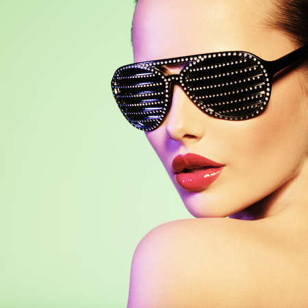 color model: Fashion portrait of  woman wearing black sunglasses with diamonds and red lips