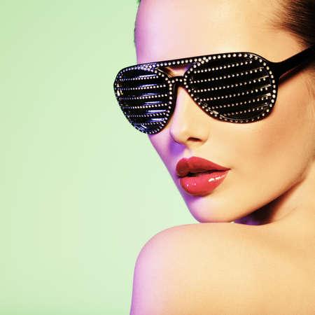 modelos negras: Retrato de mujer con gafas de sol negras con los diamantes y los labios rojos Foto de archivo