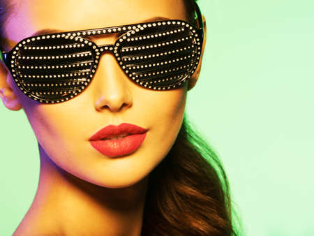 saturated color: Fashion portrait of  woman wearing black sunglasses with diamonds and red lips