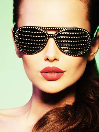 studio model: Fashion portrait of  woman wearing black sunglasses with diamonds and red lips