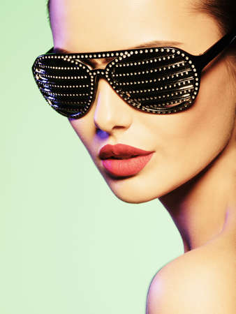 bright colors: Fashion portrait of  woman wearing black sunglasses with diamonds and red lips