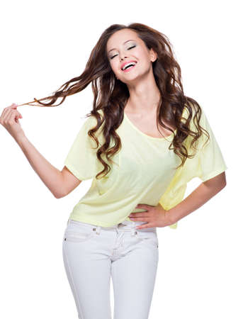 long brown hair: Young happy expressive woman with long brown curly hair posing over white background. Full portrait fashion model at studio.