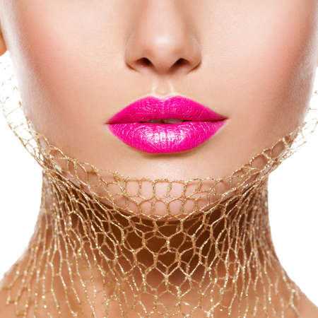 Female lips with pink lipstick and golden veil on the neck. closeup.