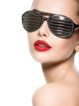 Módní portrét ženy nosí černé sluneční brýle s diamanty a červené rty