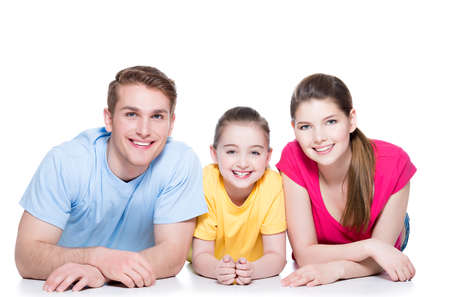 Portrait of happy smiling family with child sitting in colorful shirt lying on the floor at studio - isolated on white.