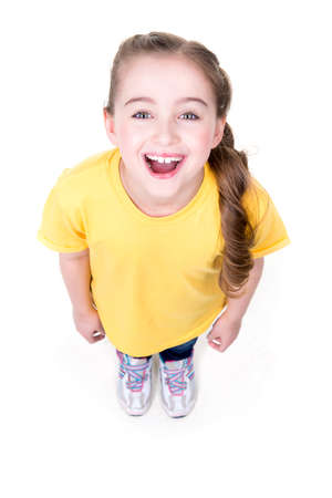 up view: Portrait of cheerful little girl looking up in yellow t-shirt. Top view. Isolated on white background.