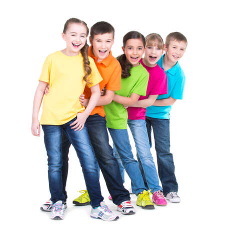 standing together: Group of happy children in colorful t-shirts stand behind each other on white background.