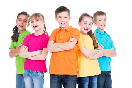 Groep van lachende kinderen met gekruiste armen in kleurrijke t-shirts staan samen op een witte achtergrond. Stockfoto