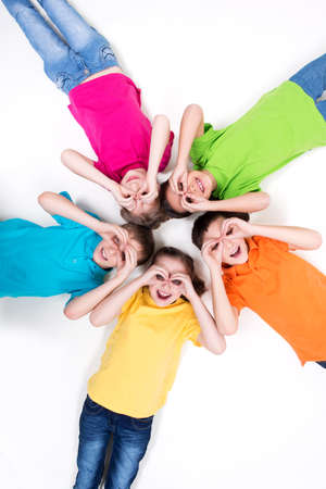 child boy: Five happy children lying on the floor in a circle with hands near eyes in bright t-shirts. Top view. Isolated on white.