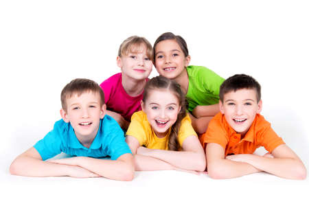 Five beautiful smiling kids lying on the floor in bright colorful t-shirts -  isolated on white. Stock Photo