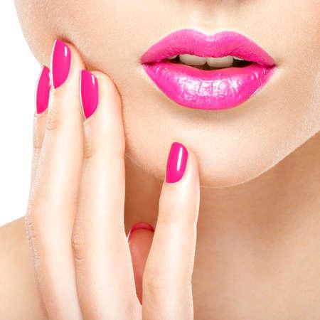 Gros plan main femme avec ongles roses près des lèvres. Ongles avec manucure rose