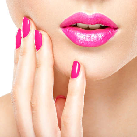 Nahaufnahme Frau Hand mit rosa Nägel in der Nähe von Lippen. Fingernägel mit rosa Maniküre