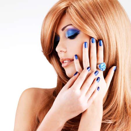 retrato de una bella mujer con las uñas de color azul, maquillaje azul y cabellos rojos sobre fondo blanco Foto de archivo