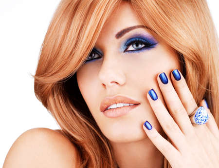 long hairs: portrait of a beautiful woman with blue nails, blue makeup and  long red hairs  on white  background Stock Photo
