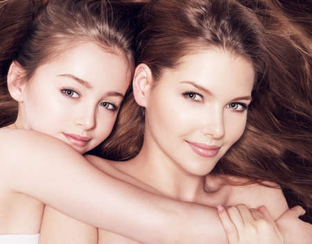 Beautiful young mother with a small daughter 8 years embrace each other at studio Stock Photo