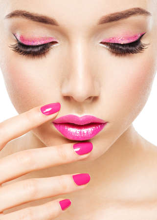 pink nails: Beautiful woman face with pink makeup of eyes and nails. Glamour fashion model portrait