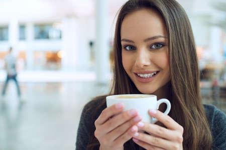 capuchino: mujer de tomar café en la mañana en el restaurante de enfoque suave. chica linda con la taza de té sonriendo. Señora alegre disfrutar y relajarse LANG_EVOIMAGES