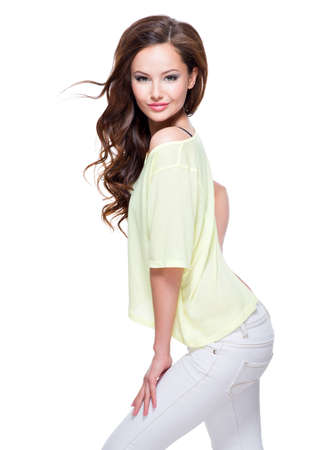 dishevel: Young beautiful pretty fashion model in yellow shirt and white trousers  with long  hair posing over white background.