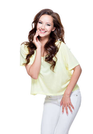 joyfull: Young happy expressive woman with long brown curly hair posing over white background. Full portrait fashion model at studio.
