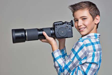 telephoto: Boy holds big photo camera with telephoto lenses LANG_EVOIMAGES