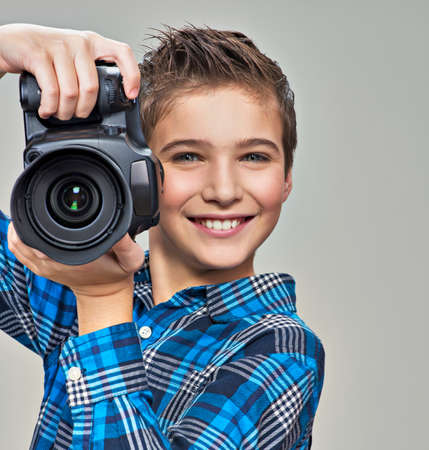 photo pictures: Boy with photo camera taking pictures. Portrait of the caucasian boy  with digital camera in hands