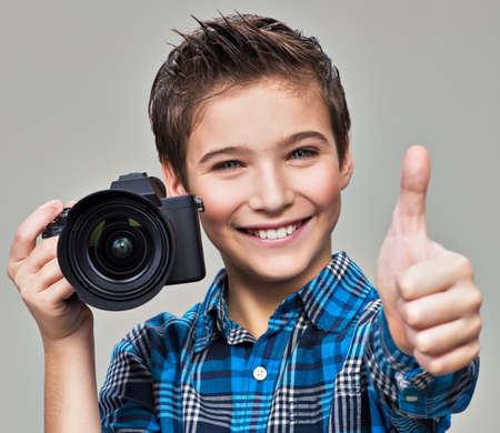 dslr camera: Boy with camera taking pictures. Happy fun boy  with dslr camera showing the thumb up LANG_EVOIMAGES