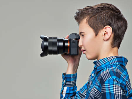 photo pictures: Boy with photo camera taking pictures. Teen boy  with dslr camera photographing. Profile portrait LANG_EVOIMAGES