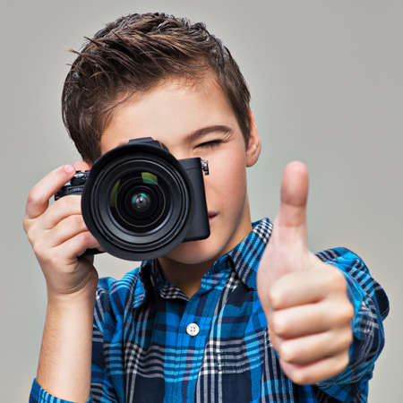 dslr: Boy with photo camera taking pictures. Teenager  boy  with dslr camera shows the thumb up
