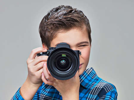 photo pictures: Boy with photo camera taking pictures. Teenager  boy  with dslr camera photographing