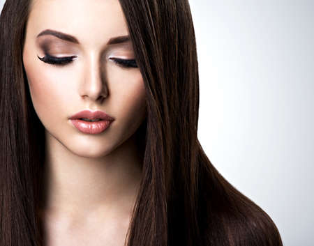 Face of beautiful young woman with brown make-up and  straight  hair Stock Photo