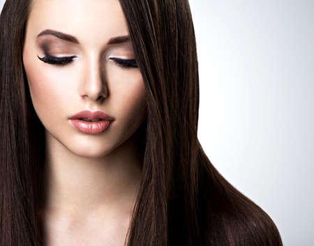Gezicht van mooie jonge vrouw met bruine make-up en steil haar Stockfoto