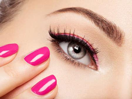 目の近くのピンクの爪を持つ女性顔をクローズ アップ。ピンクのマニキュアで爪