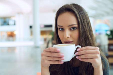 tomando café: mujer de tomar café en la mañana en el restaurante de enfoque suave. Mujer elegante en un café