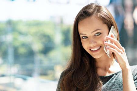 Happy young  woman speaking by cellphone indoor. Attractive caucasian girl with mobile phone in the shop.