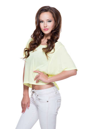 Young beautiful pretty fashion model in yellow shirt and white trousers  with long  hair posing over white background.