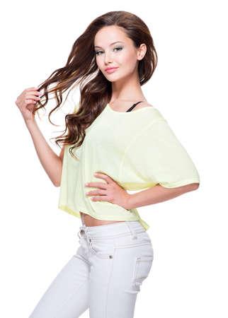 ojos negros: Joven y bella modelo de moda bonita camiseta amarilla y pantalón blanco con el pelo largo que presenta sobre el fondo blanco.