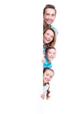 niñas sonriendo: Familia joven con la que mira hacia fuera de la bandera - aislados en un fondo blanco Foto de archivo