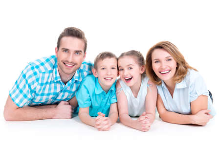 lying down on floor: Caucasian happy smiling young family with two children lying down on the  floor