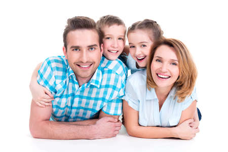 Caucasian happy smiling young family with two children lying down on the  floor photo